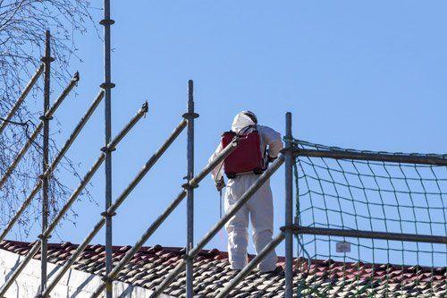 Tecnico bonifica un tetto con tuta protettiva e lancia