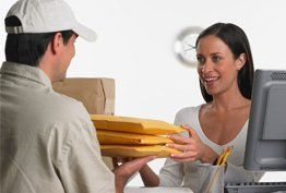 A courier handing a lady her parcels