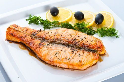 Piatto di pesce con un tocco di timo, limone e olive nere