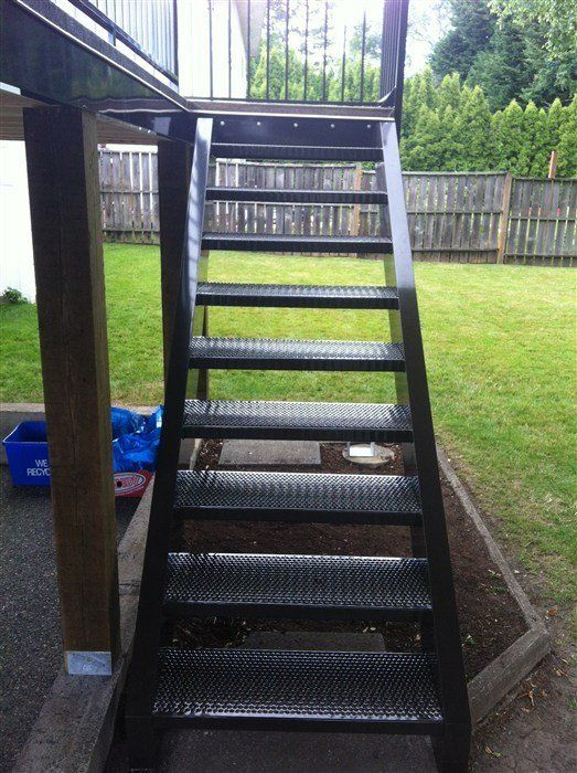 Black metal stairs attached to wooden deck