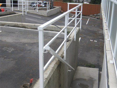 White railing with square smooth top profile attached to concrete wall