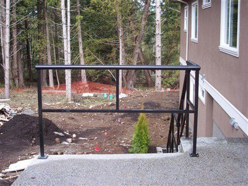 Black round railing attached with concrete porch