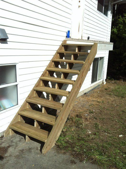Medium stain wooden stairs attached to white wood siding house