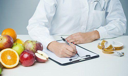 un nutrizionista con un camice bianco sta scrivendo su rilievo di scrittura, sulla sinistra c'e' della frutta e sulla destra un metro di gomma
