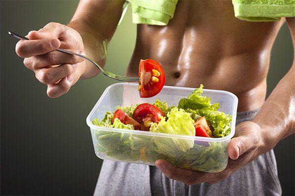 un uomo a torso nudo con un asciugamano verde attorno al collo mentre sta mangiando dell'insalata con dei pomodori