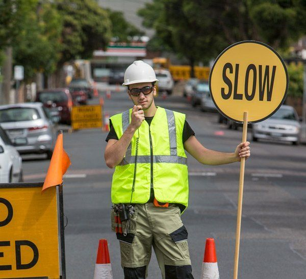 traffic control worker with slow sign