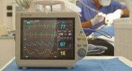 primo piano di parametri vitali su monitor, dentisti che operano paziente sullo sfondo