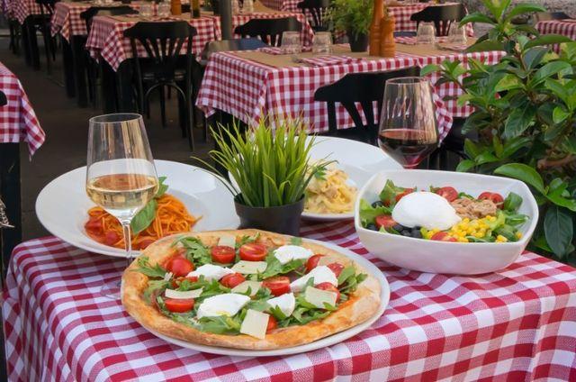 un tavolo con una pizza, insalata e due piatti di pasta
