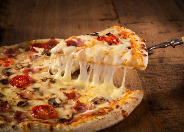 una pizza bianca con funghi e pomodorini