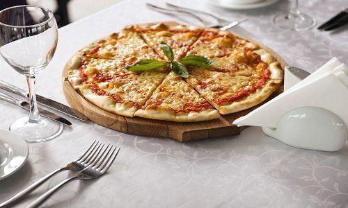 Pizza su un tagliere al centro di un tavolo apparecchiato