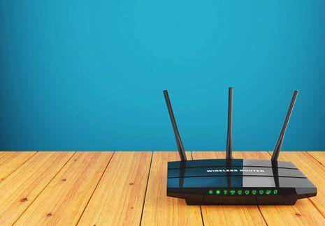 Un modem acceso con tre antenne su un piano in legno