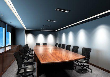 Una sala conferenze elegante con un lungo tavolo e delle sedie nere