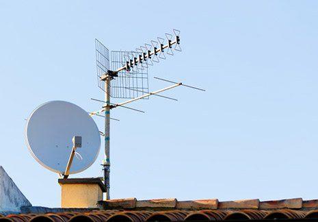 Una parabola tradizionale e una moderna installate su un tetto con tegole classiche