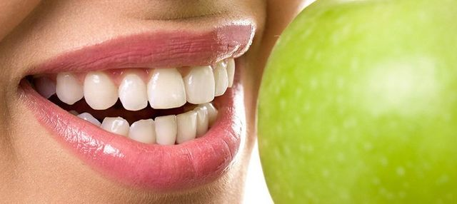 blue apple dental person with strong gums biting apple