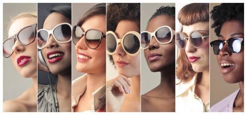 Sette volti di sette donne diverse sorridendo felici con le sue moderne occhiali da sole