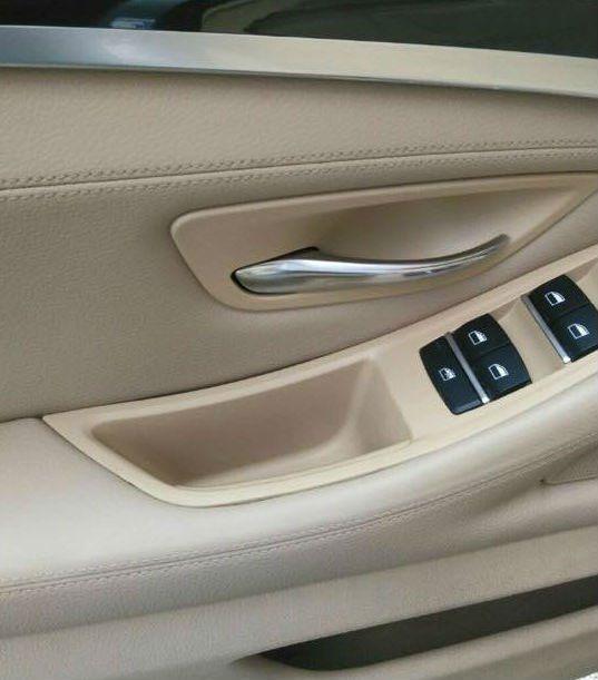 Interno della portiera di un'auto,pelle,pulsanti e manopola