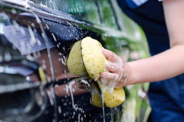 una mano con una spugna che lava una macchina