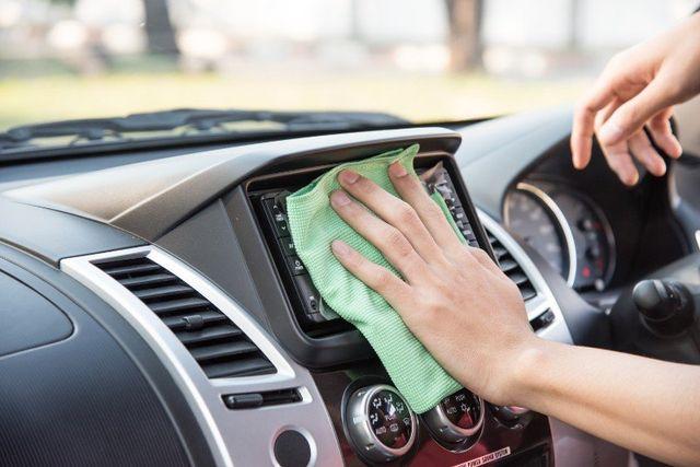 una mano con un panno che pulisce il display del computer di bordo di una macchina