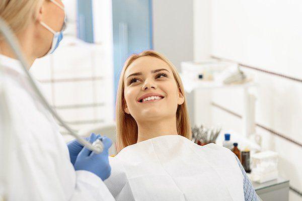 Dentista sta per effettuare una visita su una ragazza sorridente sdraiata sul lettino
