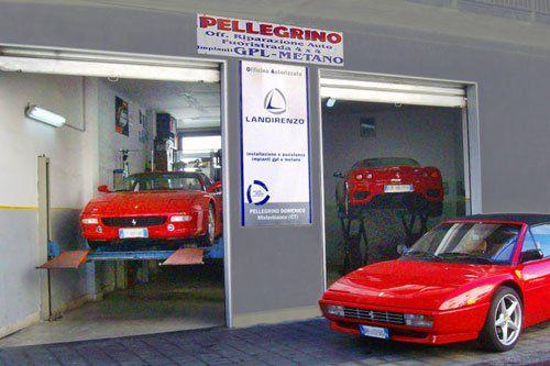 due Ferrari Testarossa sui ponti elevatori in officina e una parcheggiata davanti