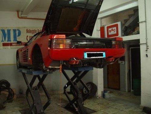 una Ferrari Testarossa su un ponte elevatore in un officina vista dal dietro