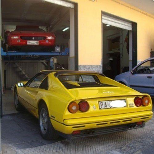 una Ferrari gialla vista da dietro e davanti un'altra Ferrari Testarossa su un ponte elevatore in officina