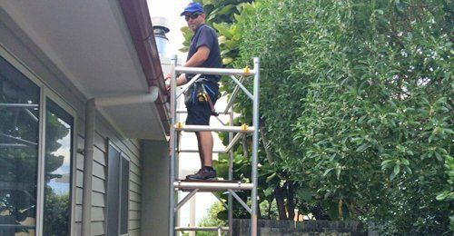 Professional repairing gutters on the roof