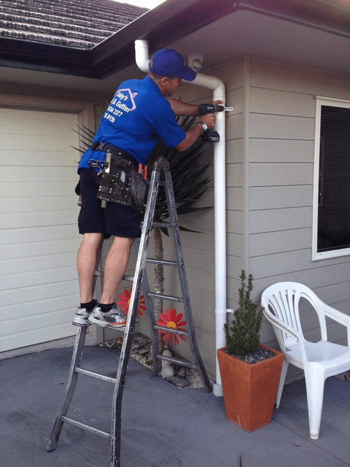 Professional working on roof and gutter repairing