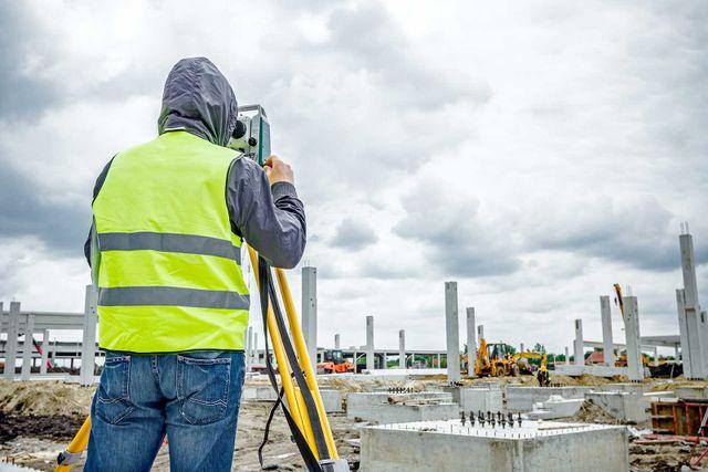 Surveyor engineer is measuring level on construction site
