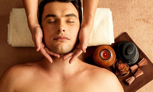 un uomo sdraiato su un lettino e le mani di una donna che le massaggiano il capo