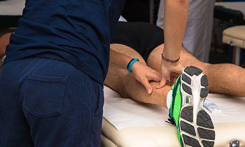 un fisioterapista che massaggia la caviglia di un ragazzo sdraiato a pancia in giu'