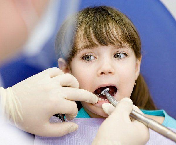 Dentista che cura i denti di una bambina