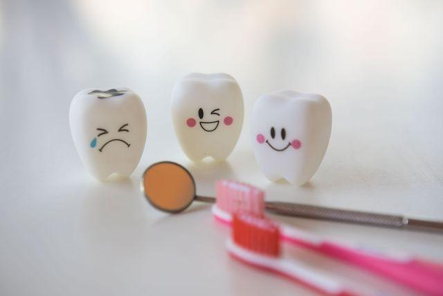 Tre modellini di denti giocattolo, uno specchietto da dentista e due spazzolini rosa