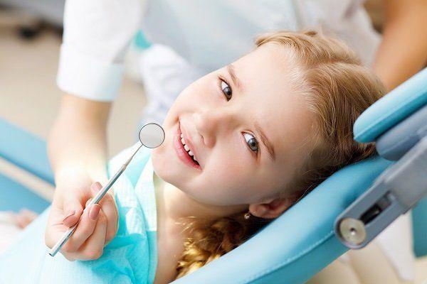 Bambina seduta sulla poltrona del dentista
