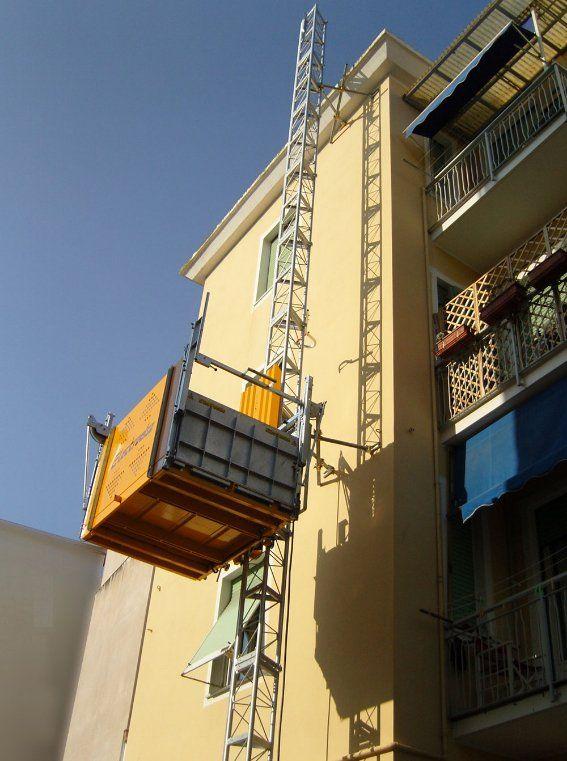 vista di un condominio alto color beige e una piattaforma elevatrice in alto