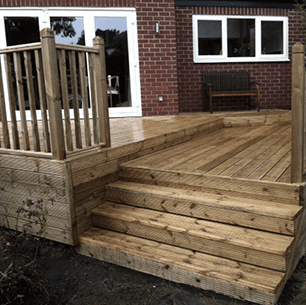 decking, wooden steps and balustrade with bi-fold patio doors visible