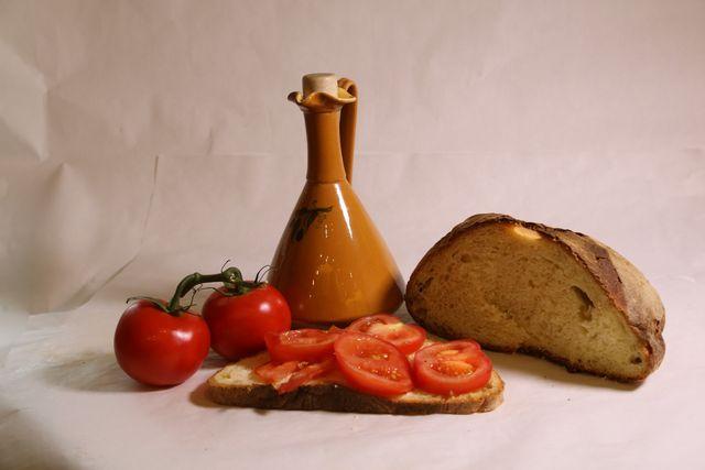 Olio d'oliva, un tozzo di pane, due pomodori e una bruschetta