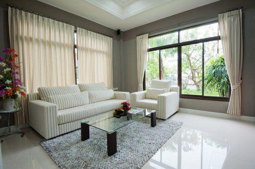 un salotto con un divano e una poltrona di color bianco e un tavolino di vetro