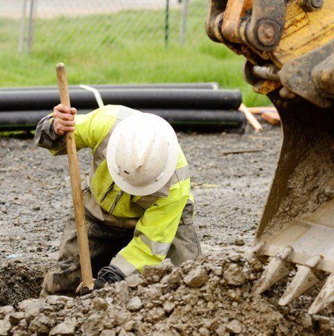 operaio con mazza e caschetto impegnato in uno scavo