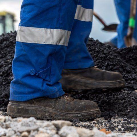 dettaglio delle scarpe antifortunio di un operaio con tuta blu