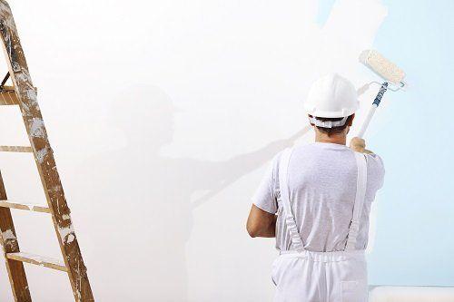 Operatore dipingendo la parete di bianco con un rullo