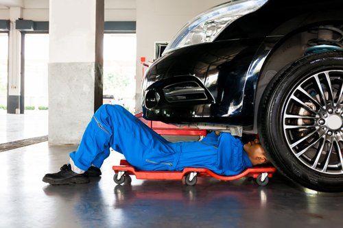 Meccanico in uniforme blu sdraiato che lavora sotto l'automobile in garage auto di servizio
