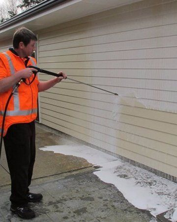 Professional doing the cleaning of the exterior wall
