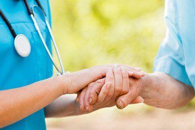 Un medico che tiene la mano di una persona anziana