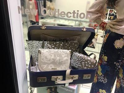 assortimento borsette da donna dentro a valigia in vetrina