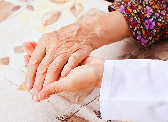 Old lady holding a hand of an individual