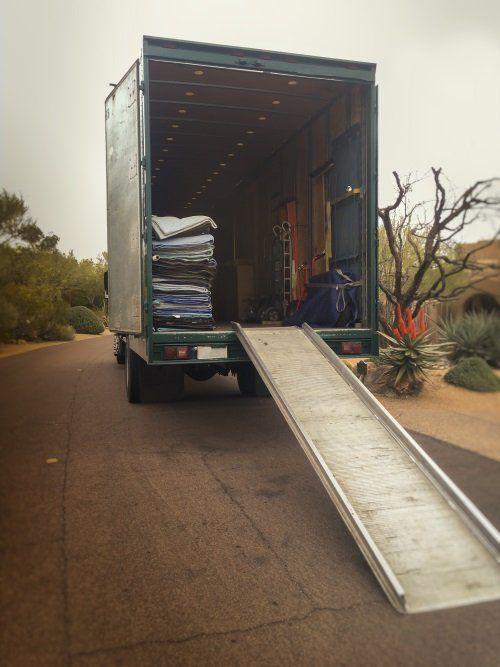 Camion aperto con la rampa e il materiale necessario per proteggere il trasporto