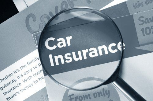 Car insurance paper with a magnifying glass on top