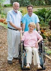 donna sulla sedia a rotelle tiene la mano ad un uomo vicino a un infermiere