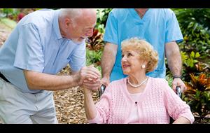 donna sulla sedia a rotelle tiene la mano e parla ad un uomo anziano